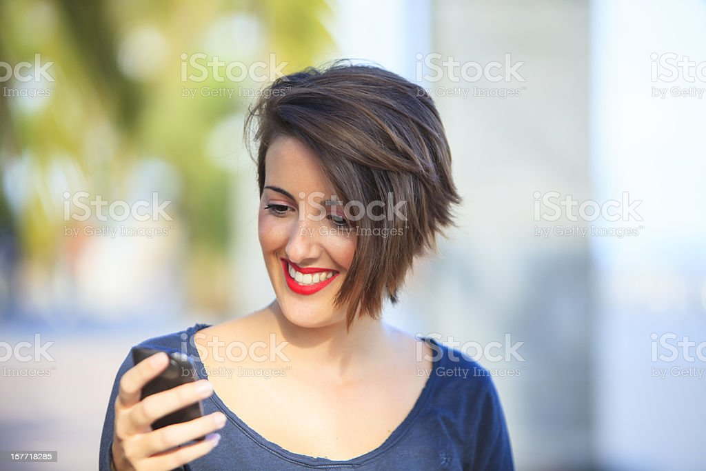 Woman smiling as she looks at her smartphone royalty-free stock photo