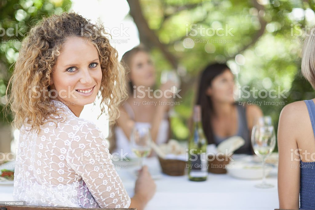 Woman smiling at table outdoors stock photo
