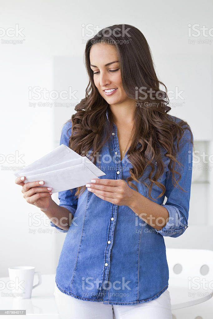 A woman smiling down at the letter in her hand stock photo