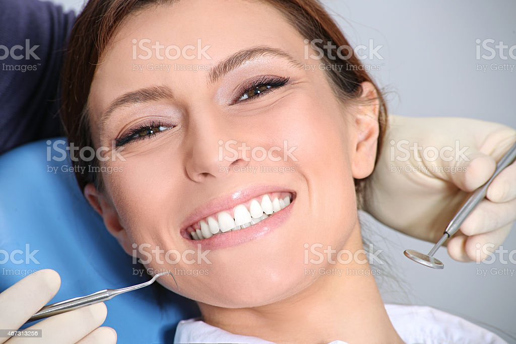 Woman smiling during a teeth examination at the dentist stock photo