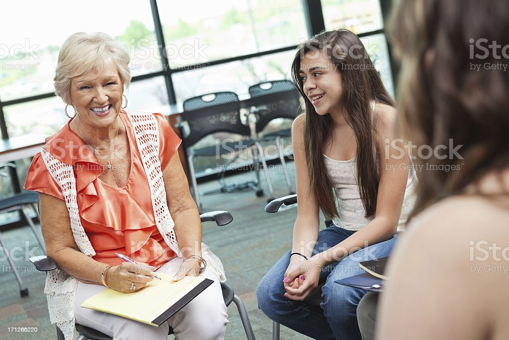 Woman smiling during counseling session with teenagers royalty-free stock photo
