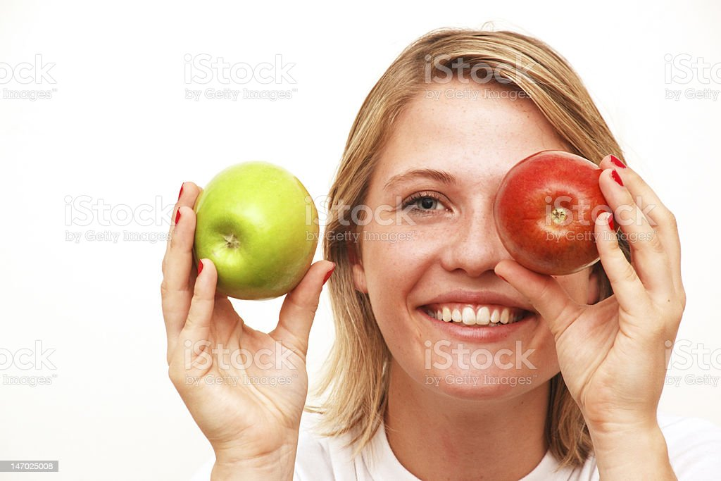 Woman smiling holding a red and green apple royalty-free stock photo