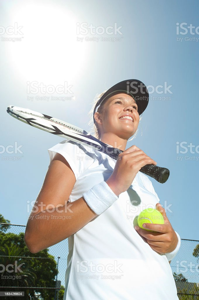 Woman smiling holding a tennis racquet royalty-free stock photo