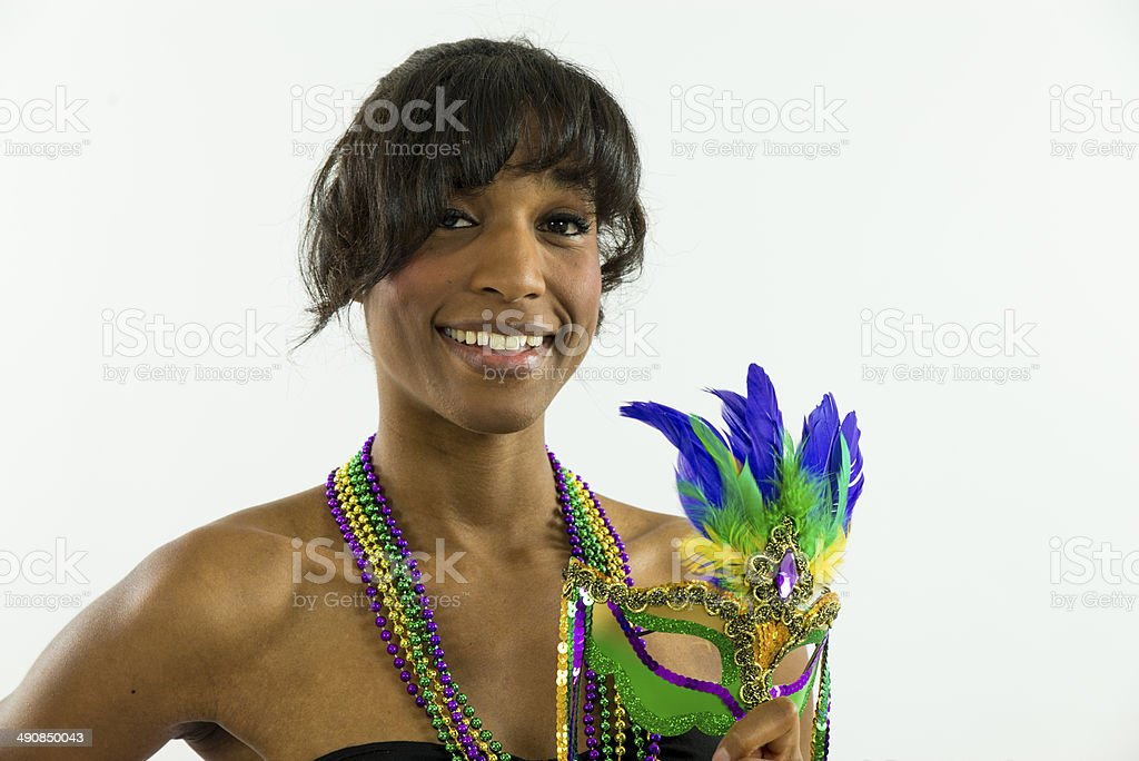 Woman smiling holding Mardi Gras mask looking at camera stock photo