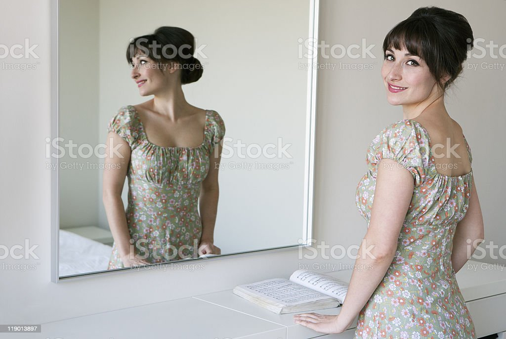 Woman smiling in front of mirror stock photo
