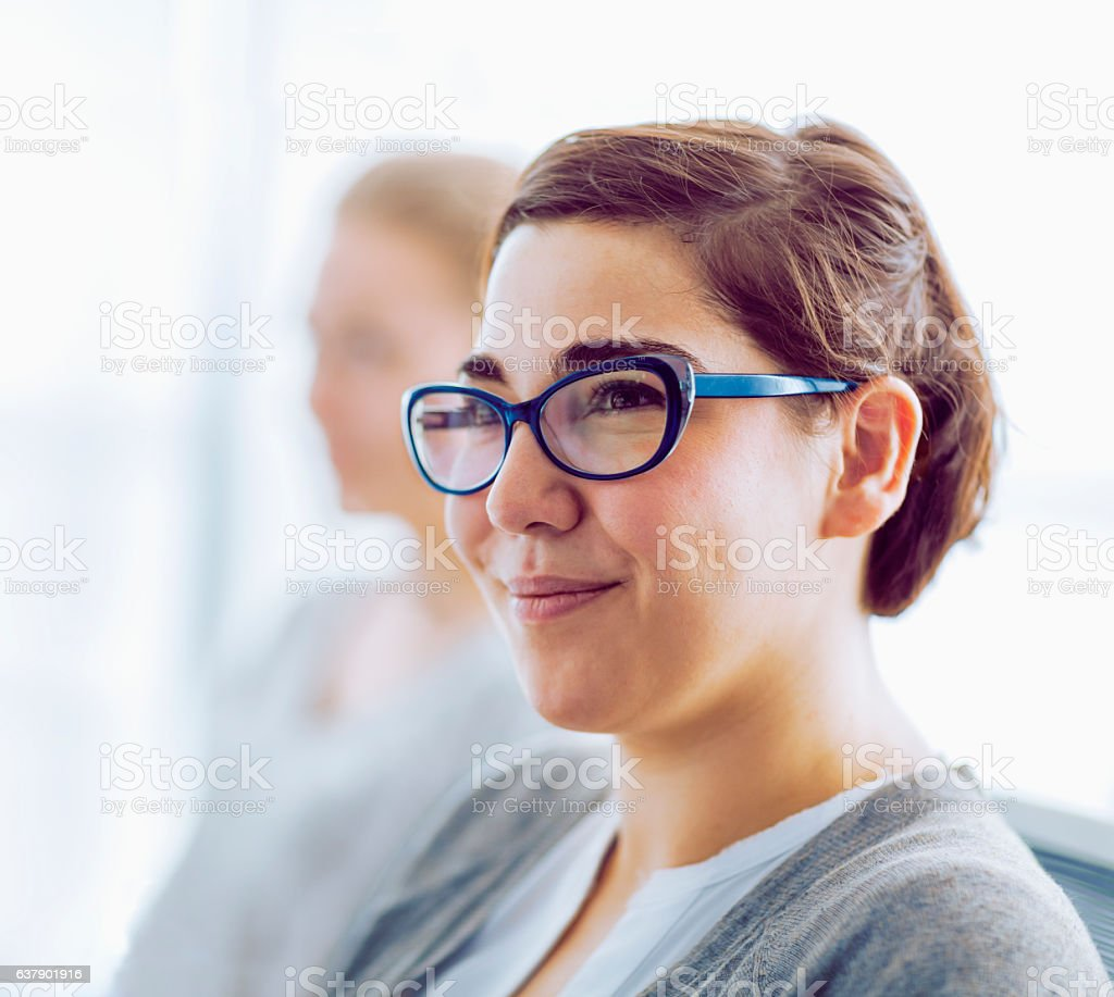 Woman smiling in office meeting stock photo