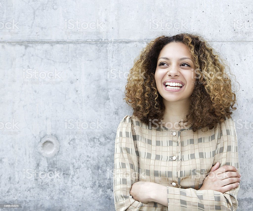 Woman smiling outdoors with arms crossed stock photo