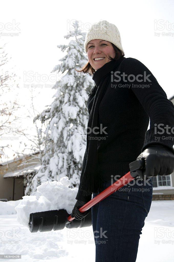 Woman Smiling Snow Shoveling royalty-free stock photo