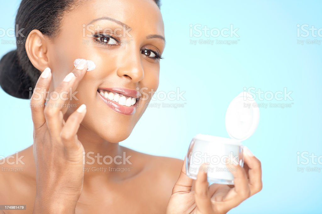 Woman smiling while applying cosmetic cream to her cheek royalty-free stock photo