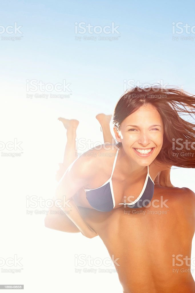 Woman smiling while being carried, wearing bikini royalty-free stock photo