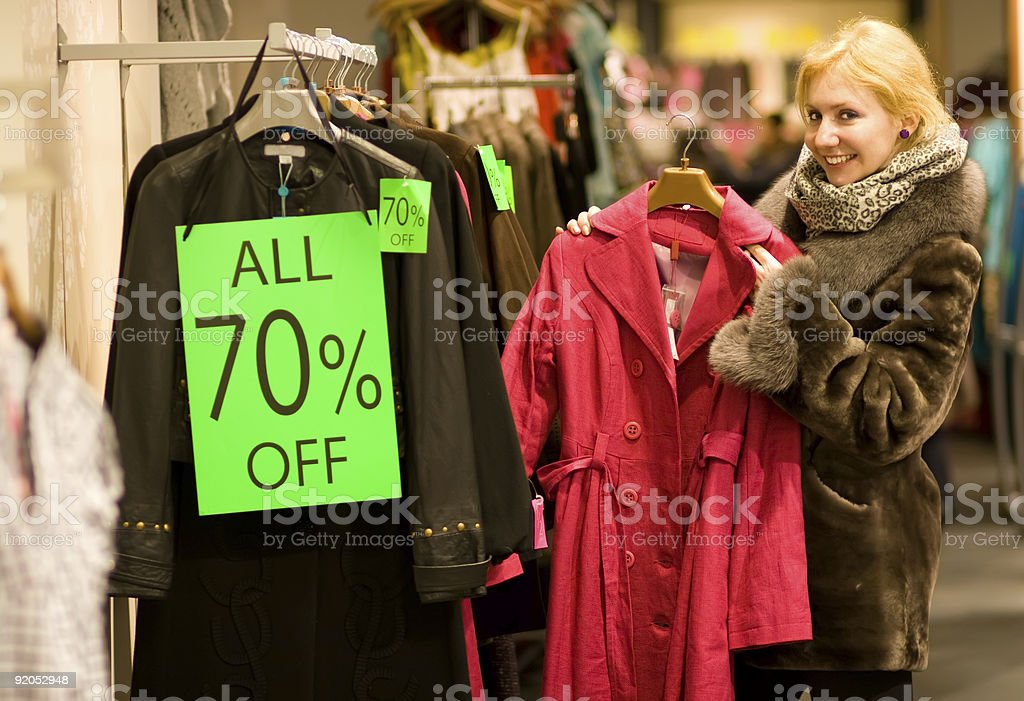 A woman smiling while going through rack of 70% off clothes royalty-free stock photo