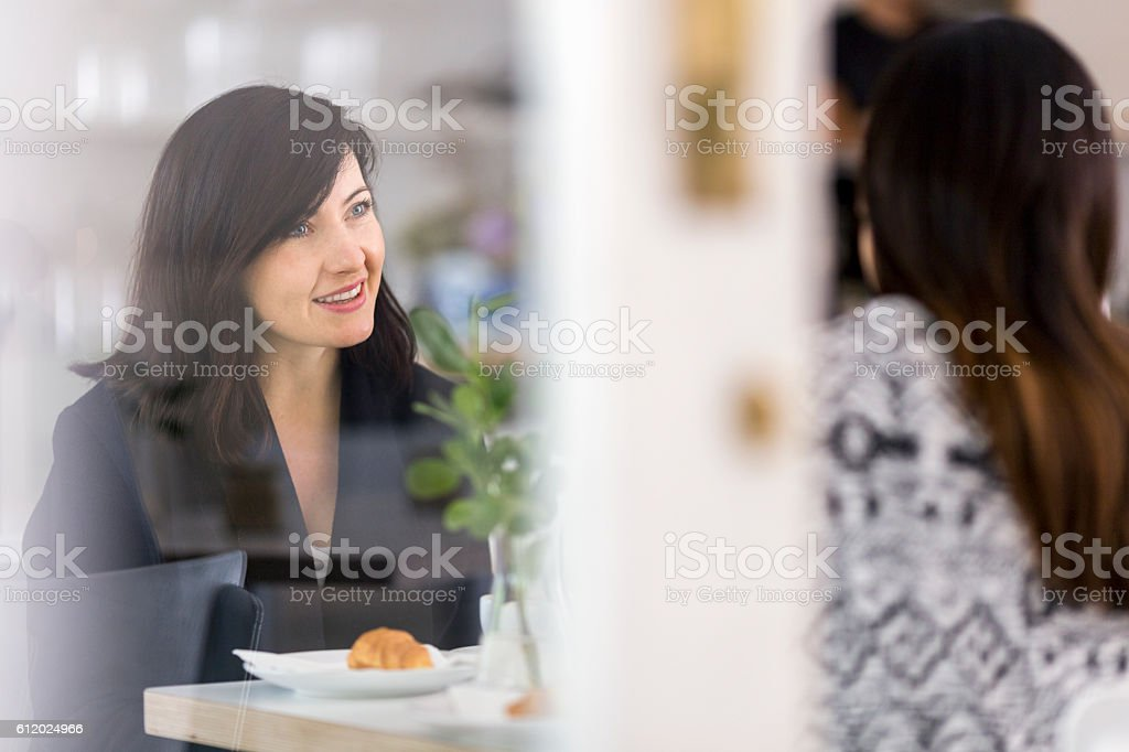 Woman smiling while looking at friend in cafe stock photo