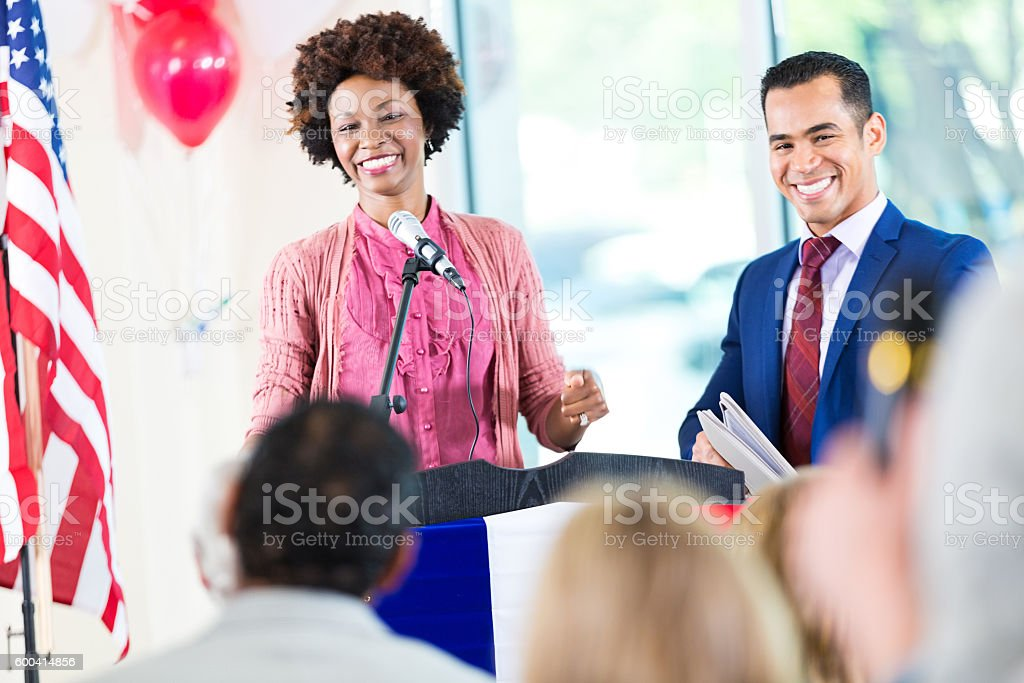 Woman smiling while speaking at political rally and supporting candidate stock photo