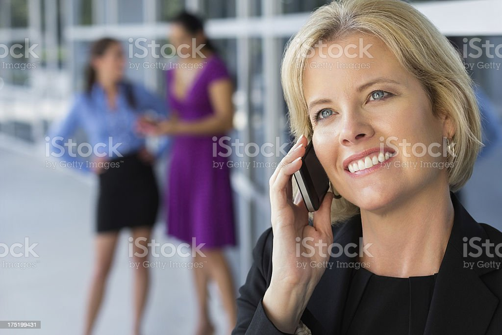 Woman smiling while talking on her cell phone royalty-free stock photo