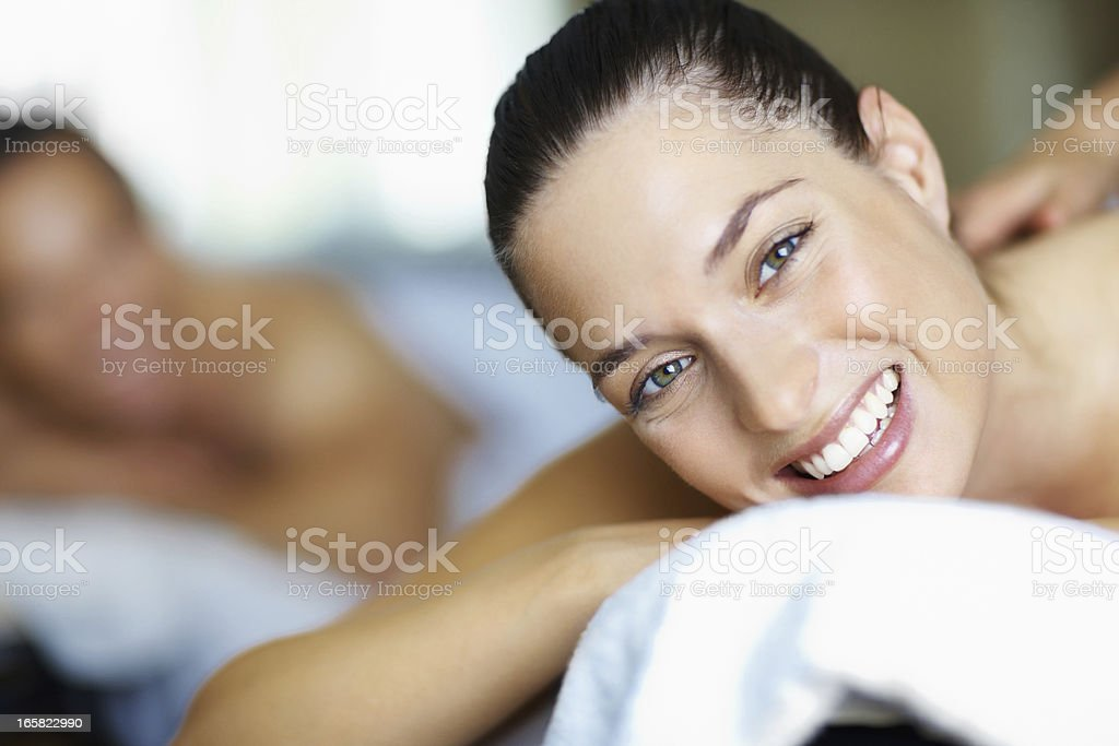 Woman smiling whilst receiving a massage royalty-free stock photo
