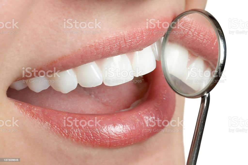 A woman smiling with a dental mirror close to her teeth stock photo