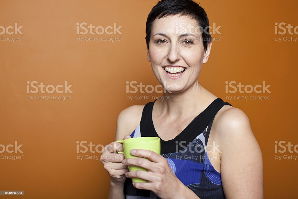 woman smiling with a green coffee mug royalty-free stock photo