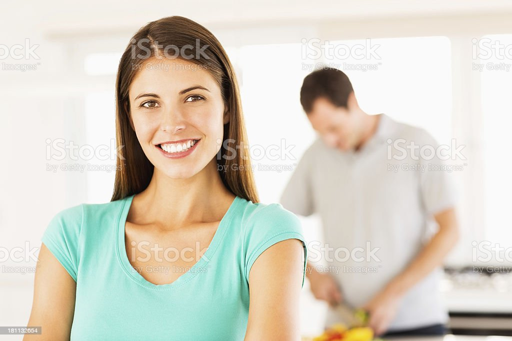 Woman Smiling With Man Cooking In background royalty-free stock photo