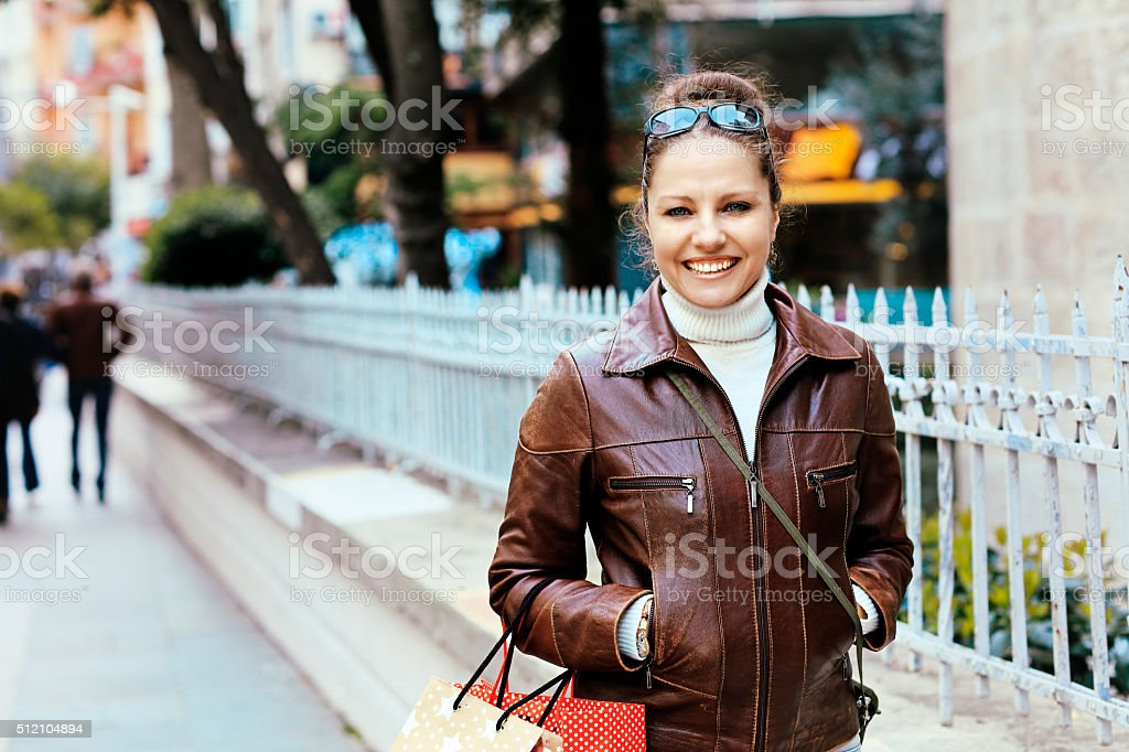 Woman smiling with shopping bags in her hands stock photo