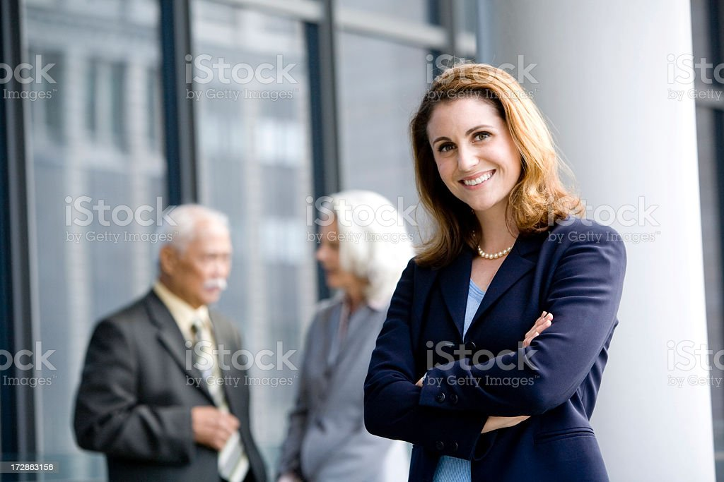 A woman smiling with two people talking in the background stock photo