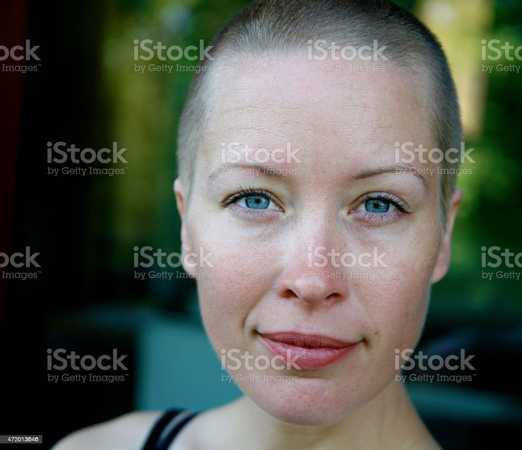 Woman smirks into the camera with clear, blue eyes. stock photo