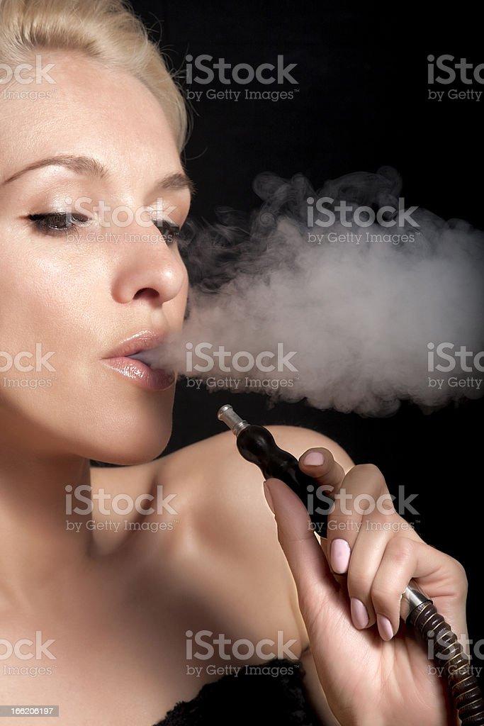 Woman smokes a hookah royalty-free stock photo