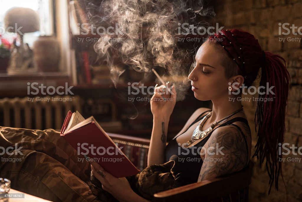 Woman smoking a cigarette while reading a book at home. stock photo