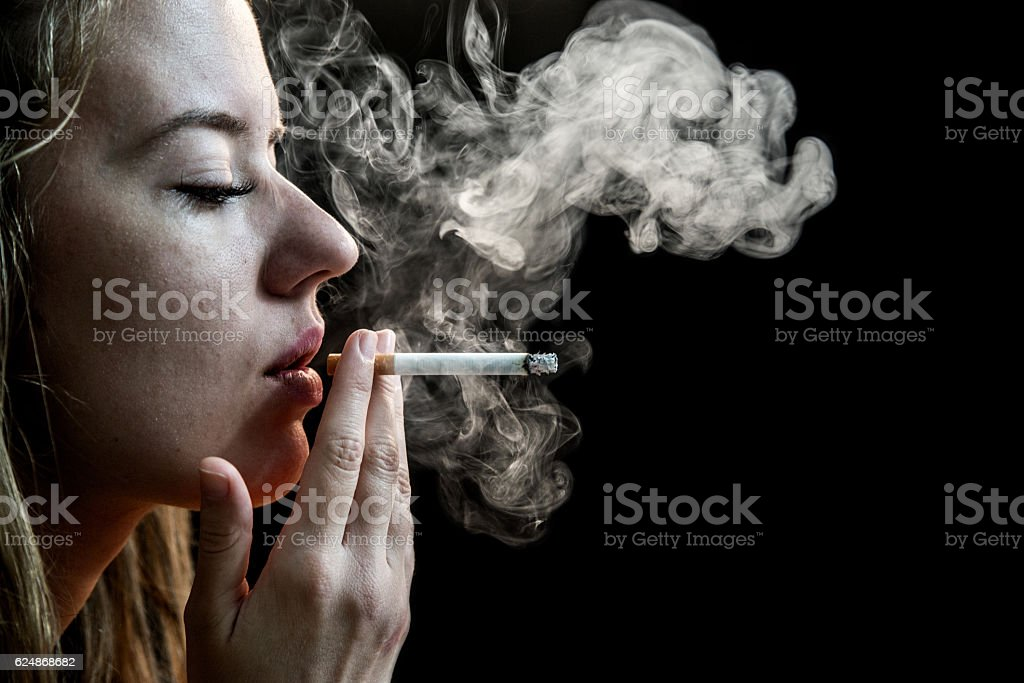 Woman Smoking a dangerous Cigarette on Black Background stock photo