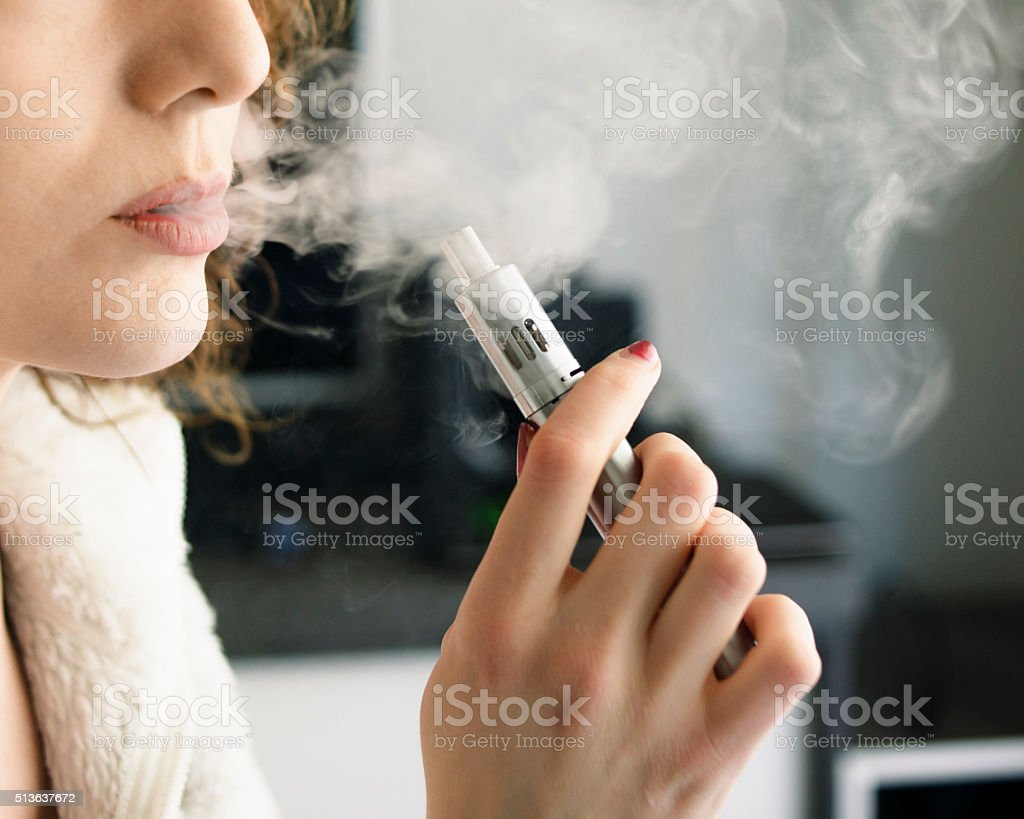 Woman Smoking an E-Cigarette stock photo