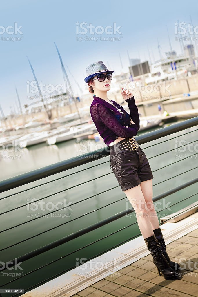 woman smoking at the dock stock photo