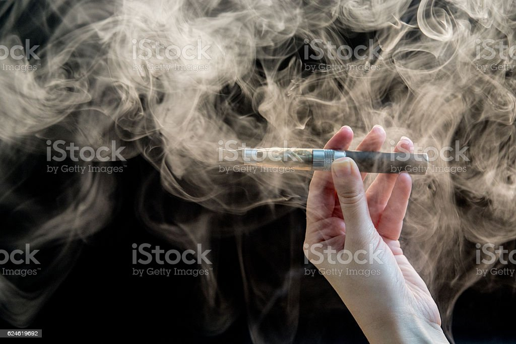 woman smoking electronic cigarette on background stock photo