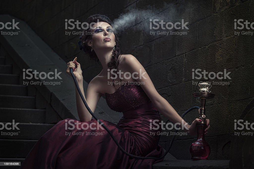 Woman smoking in Victorian purple dress stock photo