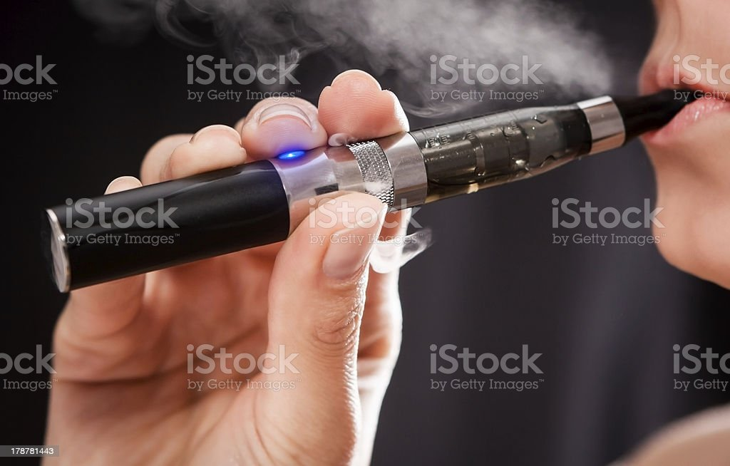 Woman smoking with electronic cigarette stock photo
