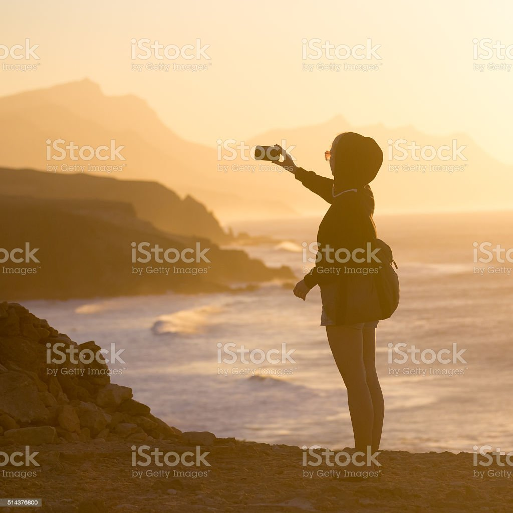 Woman snaping photo of La Pared beach in sunset. stock photo