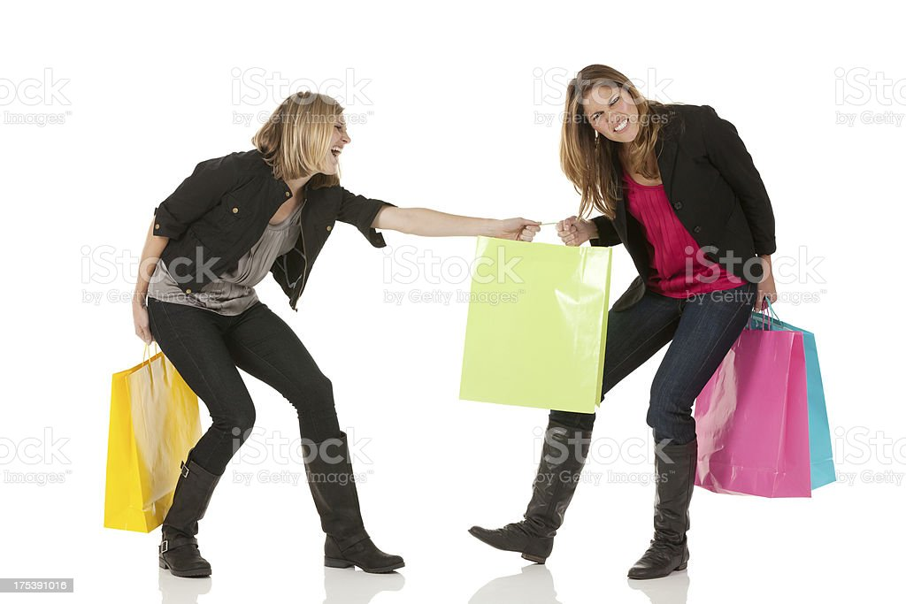 Woman snatching shopping bag from her friend stock photo