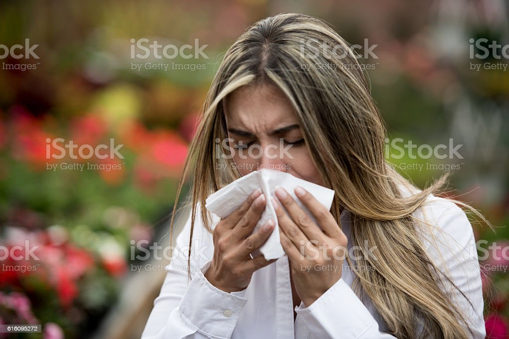 Woman sneezing at a greenhouse stock photo