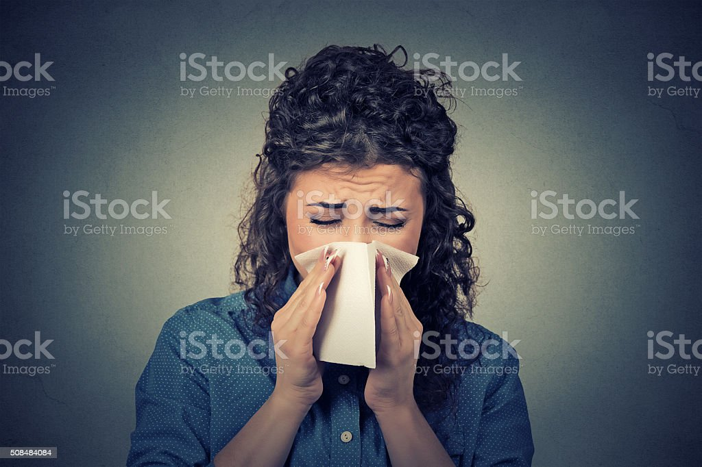 woman sneezing in a tissue blowing her runny nose stock photo