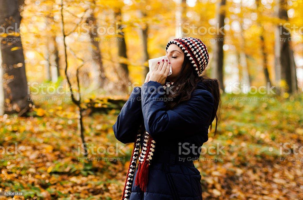 Woman sneezing in handkerchief at autumn stock photo