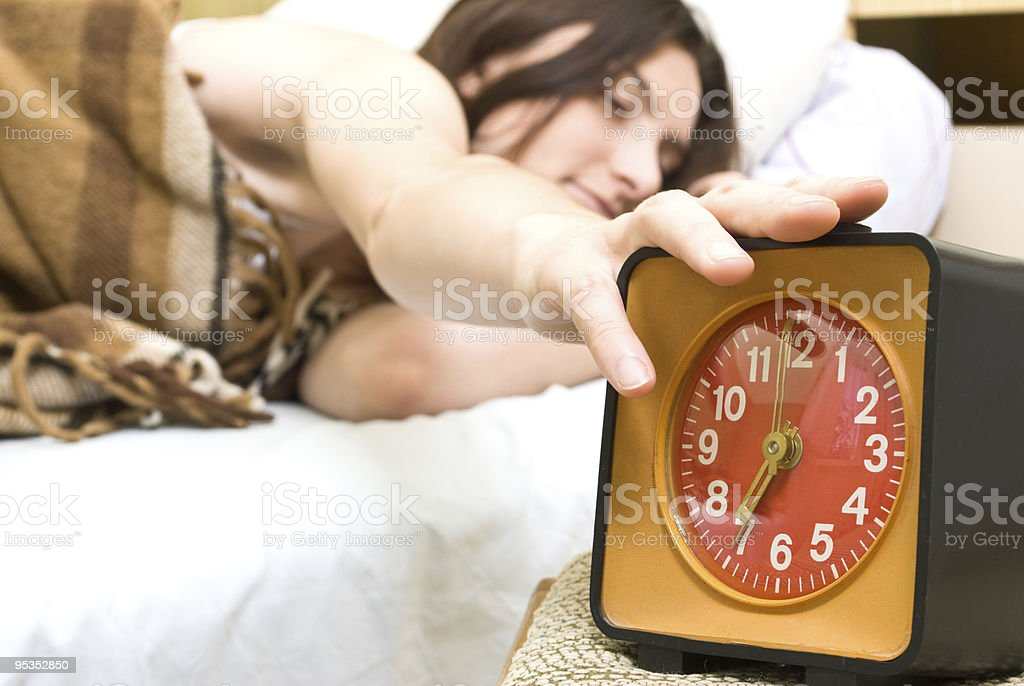 woman snoozing a alarm clock royalty-free stock photo