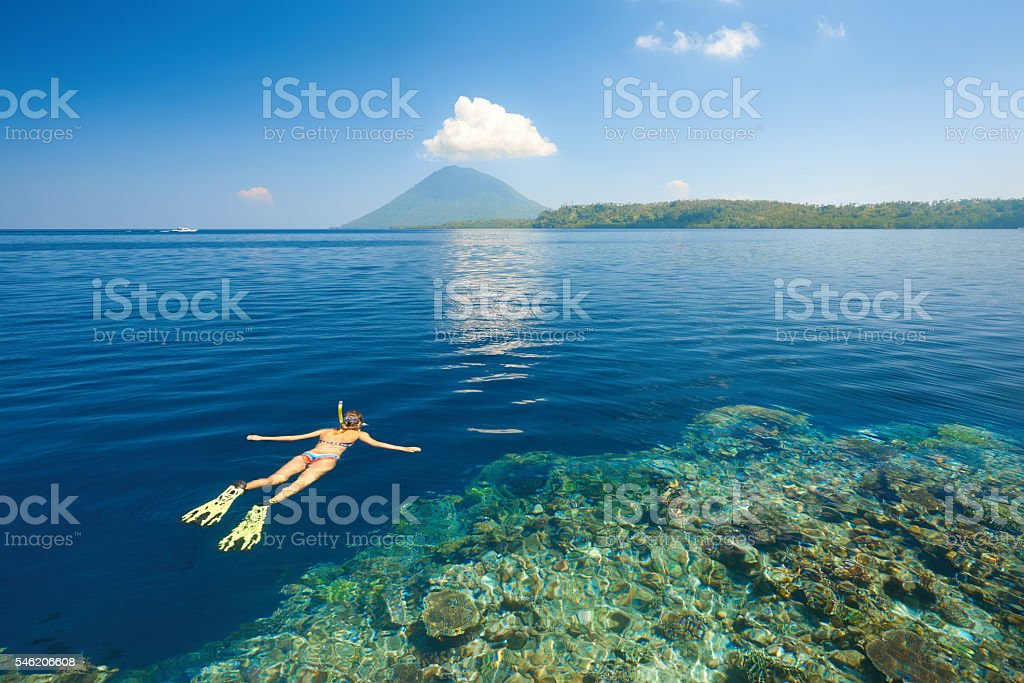 Woman snorkeling in clear tropical waters on background of island stock photo