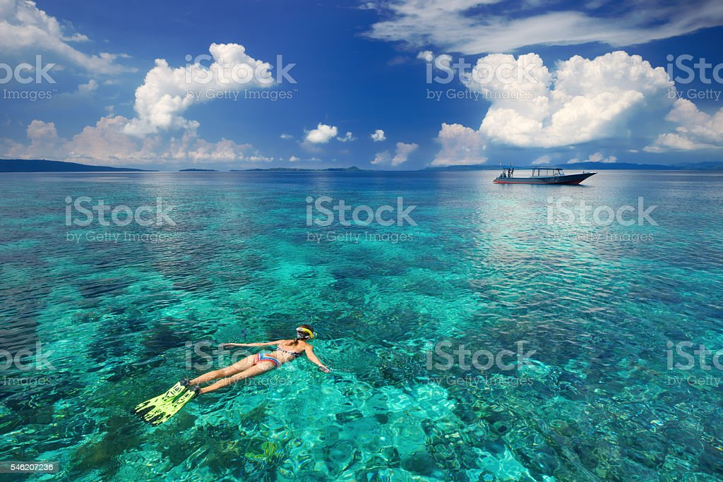 Woman snorkeling in clear tropical waters stock photo