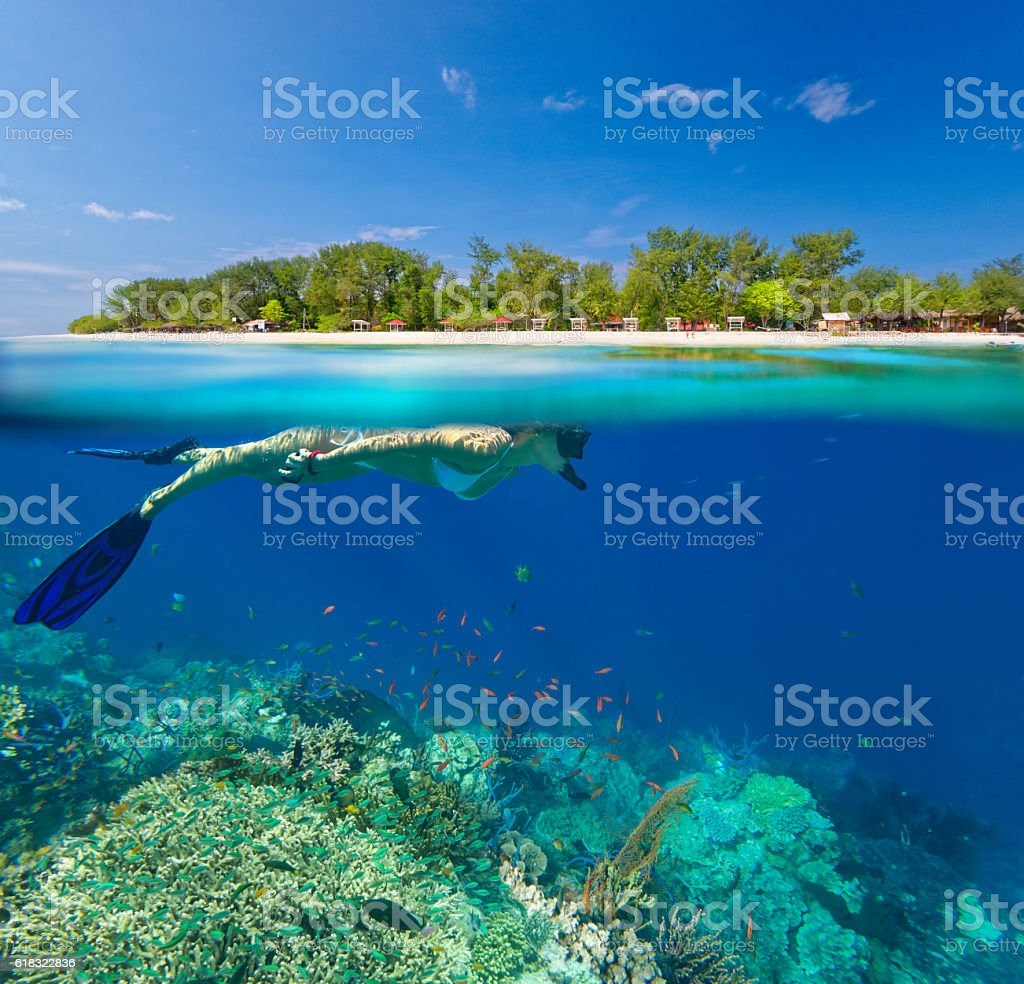 Woman snorkeling in clear tropical waterson stock photo