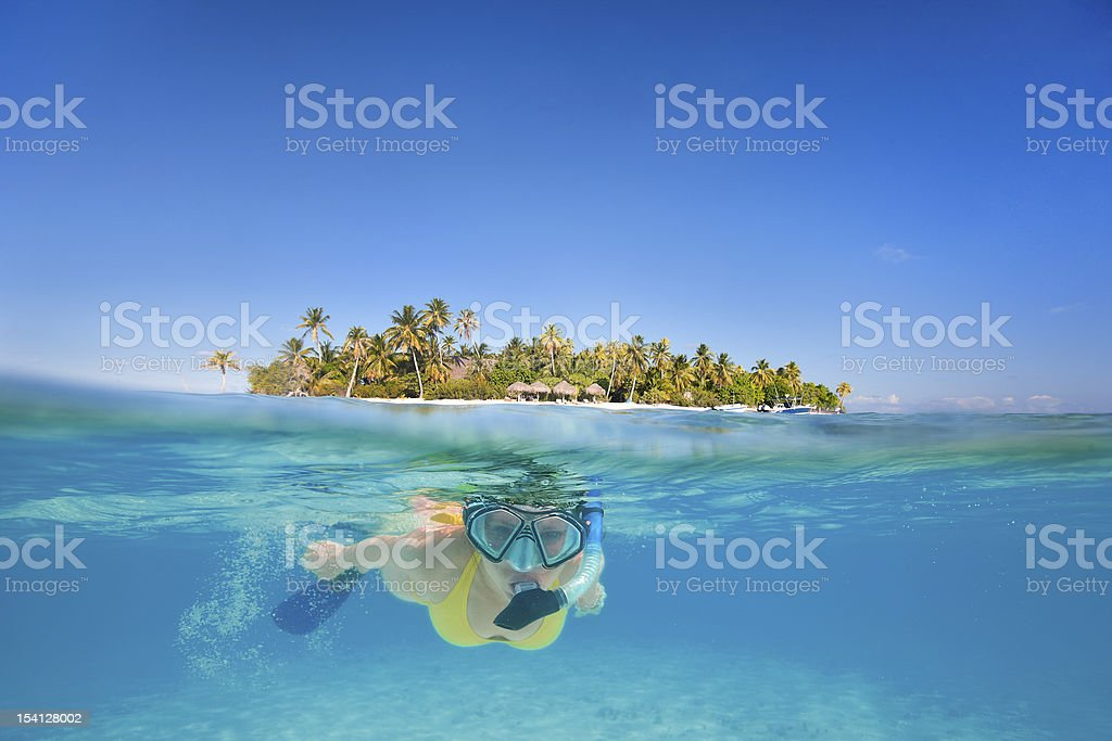 A woman snorkeling in the tropical paradise stock photo