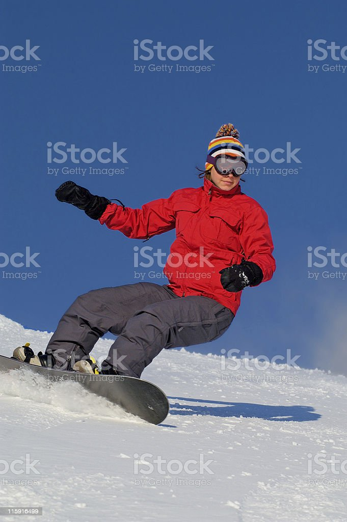 Woman snowboarding downhill in a red jacket royalty-free stock photo