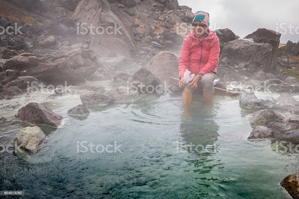 Woman soaking feet in hot spring after long hike stock photo