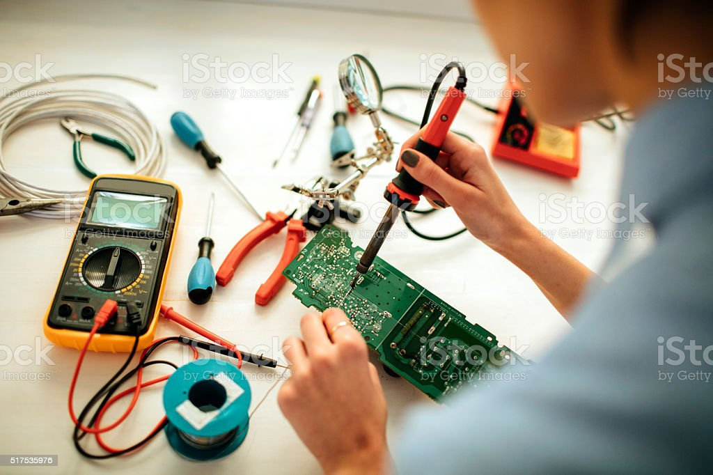Woman Soldering a circuit board in her office. stock photo