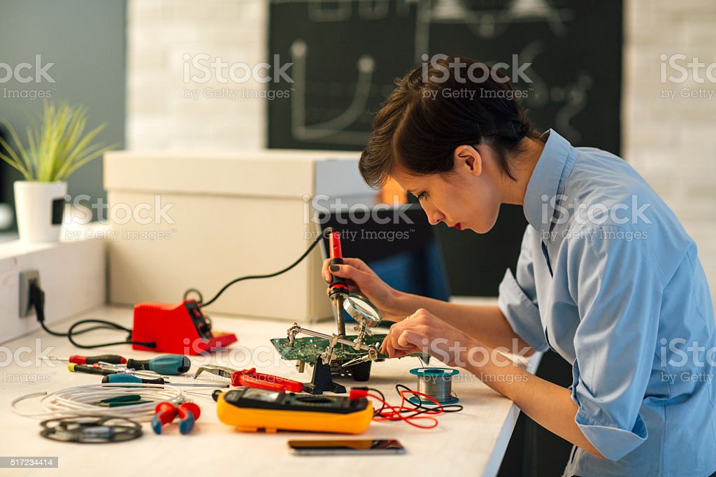Woman Soldering a circuit board in her tech office. stock photo
