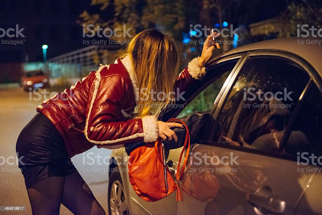 Woman soliciting someone in a car on the street stock photo