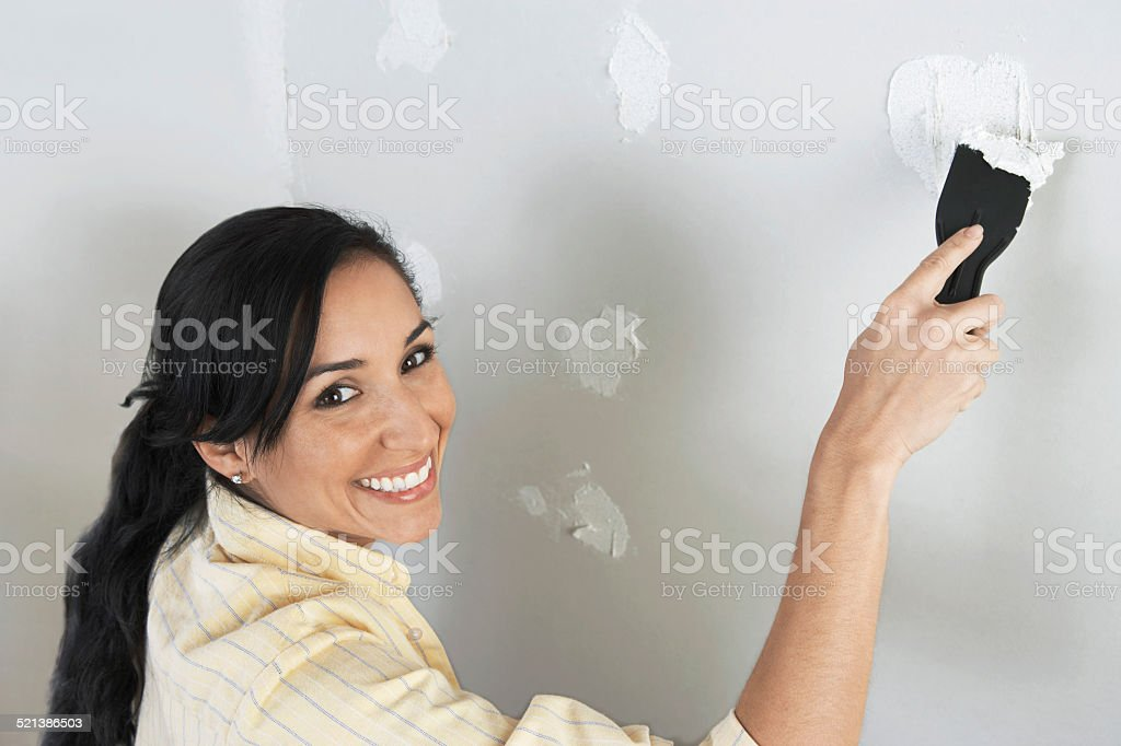 Woman Spackling Wall stock photo