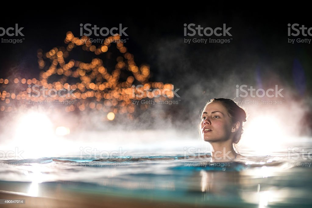 Young woman swimming in heated swimming pool during winter night.